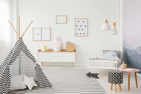 Tenda modellata vicino a sgabello all'interno della camera da letto del bambino con poster sulla parete bianca sopra l'armadio in legno Archivio Fotografico