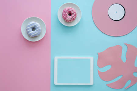 Blue doughnut on pink background and mockup of tablet next to a leaf and vinyl 版權商用圖片