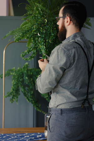 Hipster in grey shirt interested in biology holding a plant at home