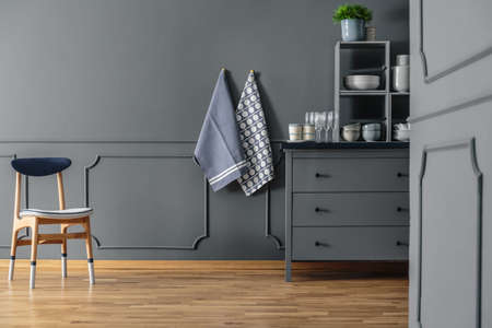 Wooden chair against grey wall with molding and textiles in kitchen interior with cabinet