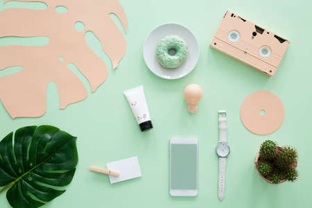 Watch between cactus and smartphone on mint desk with doughnut, peach cassette and leaf 版權商用圖片