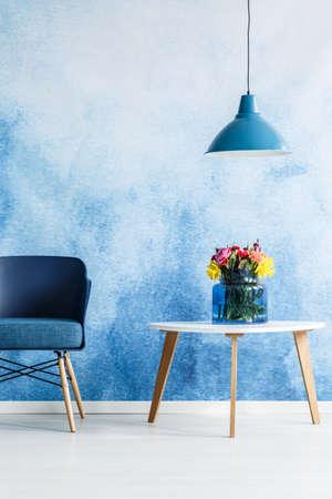 Witte tafel met bloemen naast een blauwe stoel en lamp op een ombre muur in woonkamer interieur