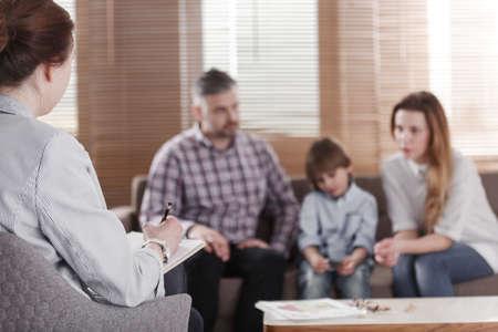 Vista trasera de la psicóloga ayudando a una familia joven con un niño a resolver problemas de desarrollo infantil. Familia sentada en un sofá en el fondo borroso Foto de archivo