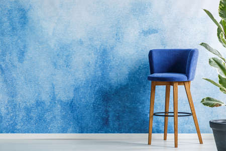 Bar stool standing in a living room interior next to a flower set on an empty wall painted with watercolor. Place your product