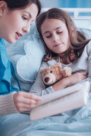 Caregiver reading a book to a sick girl with plush toy in the clinic