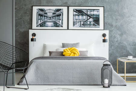 Yellow pillow on grey bed in bedroom interior with armchair and posters against concrete wall
