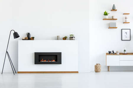 Black lamp next to fireplace in white apartment interior with copy space. Real photo Stok Fotoğraf