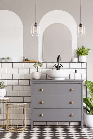 Lamps above grey cabinet with washbasin in modern bathroom interior with mirror. Real photo