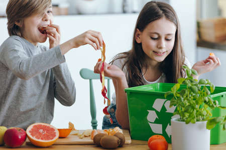 Kids playing with an apple skin while segregating waste in the kitchen Stock Photo