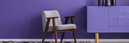 Grey armchair standing next to a purple cupboard in violet room interior with place for your table