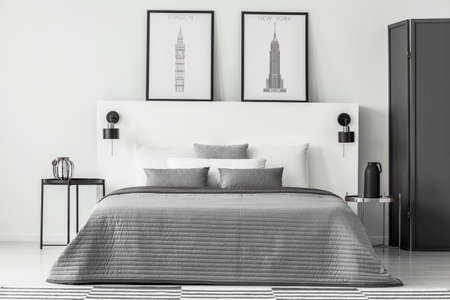 Grey bedding on bed in monochromatic bedroom interior with posters on white bedhead