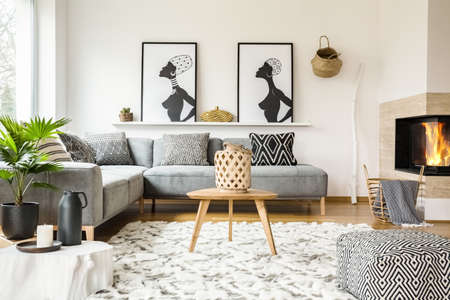 Patterned pouf next to wooden table in african living room interior with posters. Real photo
