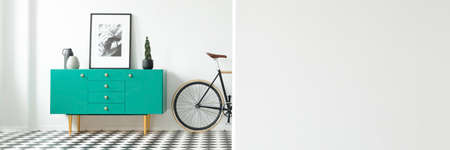 Bike standing next to a green, wooden cupboard with simple poster, potted plant and two vases in white open space room interior