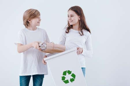 Children segregating waste, standing against white background