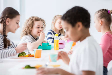 Group of children eating vegetables in the dining hall of school Stock Photo