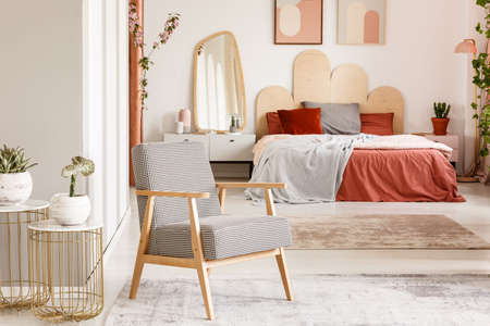 Patterned wooden armchair next to gold table in orange bedroom interior with bed. Real photo Reklamní fotografie