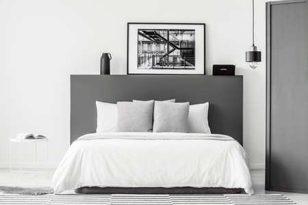 Patterned cushions on bed in grey and white bedroom interior with poster and lamp 写真素材