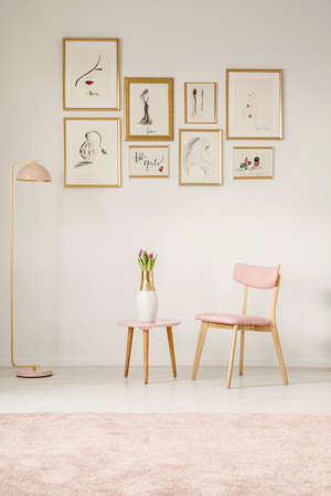 Paintings in golden frames, pink chair, table and lamp set on the white wall in a sitting area interior