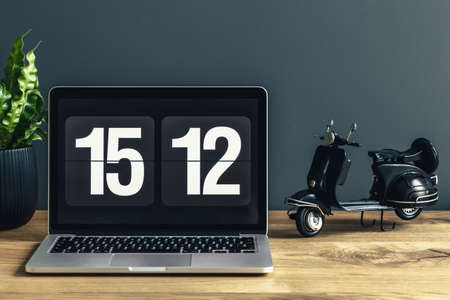 Close-up of laptop with clock on wooden desk with black toy in workspace interior
