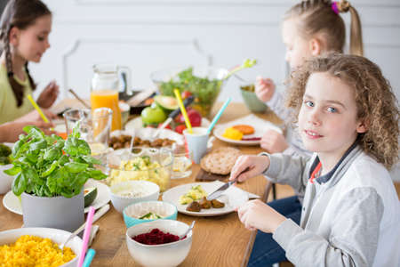 Boy eating healthy dinner during party with friends at home
