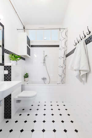 Patterned floor in white and black bathroom interior with towels, toilet and bathtub. Real photo