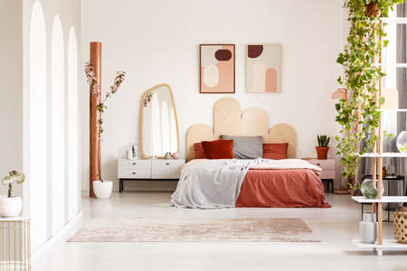 Mirror on cabinet next to orange bed under posters in bright bedroom interior with plants. Real photo Stockfoto