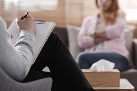 Back view of psychotherapist writing notes, assessing patient's health and giving diagnosis to a woman sitting on a couch in the blurred background during counseling session