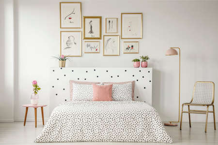 Bright bedroom interior with dotted sheets, headrest, double bed, gold accents and art gallery above Stock Photo