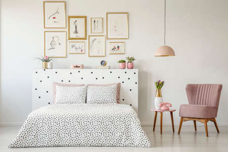 Dotted, double bed, paintings with gold frames and pink armchair set in a serene bedroom interior Stock Photo