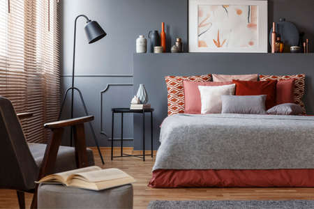 Close-up of a book on a stool next to an armchair in a bedroom interior with a comfy bed with pillows, painting and lamp