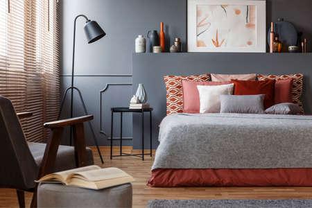 Primer plano de un libro en un taburete junto a un sillón en el interior de un dormitorio con una cómoda cama con almohadas, pintura y lámpara