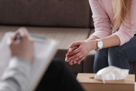 Close-up of woman's hands during counseling meeting with a professional therapist. Box of tissues and a hand of counselor blurred in the front. Stockfoto