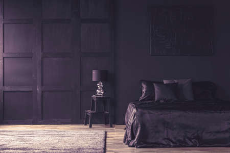 Violet filter on dark bedroom interior with bed under painting next to a lamp on wooden table 写真素材 - 102471716