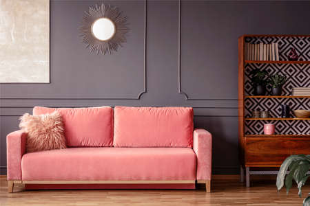 Simple, Pink Sofa With A Fur Pillow Next To A Wooden Cupboard ...