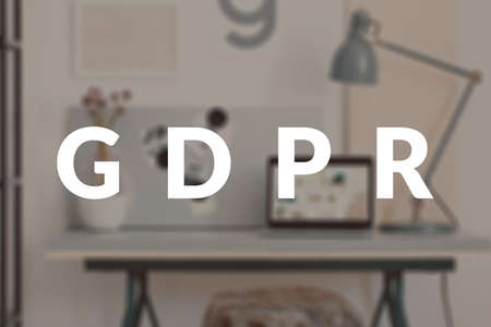 White GDPR text on blurred photo of a desk with laptop. Data security legislation concept