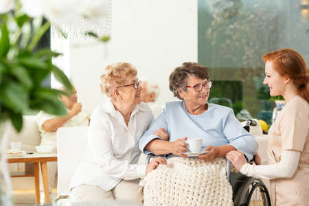 Caregiver talking to a smiling senior woman and her friend in the nursing house