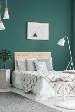 White, double bed, geometrical poster on a green wall and lamps in a comfy bedroom interior