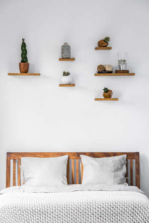 Close-up of a white wall with small decorations on shelves above a wooden headboard of a bed with pillows and blanket in a bright bedroom interior. Real photo.