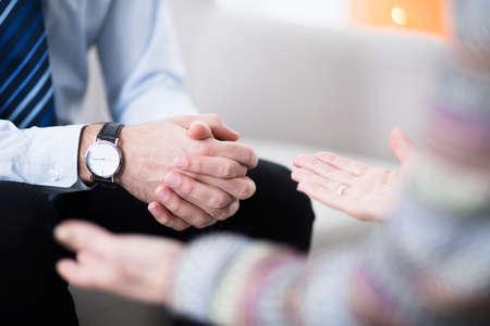 Close-up van mannelijke handen met een elegant horloge en de handen van zijn vrouwelijke therapeut Stockfoto
