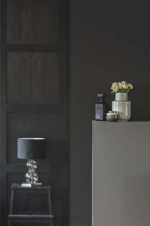 Flowers on grey headboard next to a lamp on table in simple dark living room interior with copy space