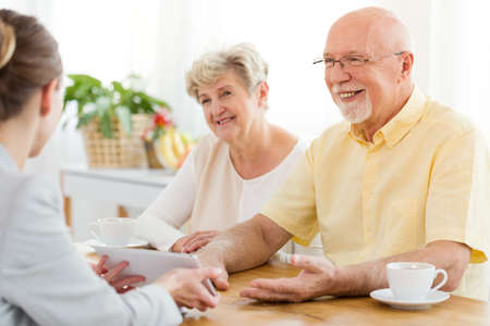 Smiling senior man and woman talking to a financial advisor about a loan Stock Photo