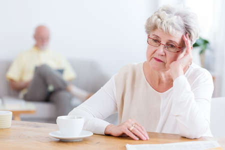 Sad elderly woman sitting at a wooden table, thinking about divorcing her husband Standard-Bild