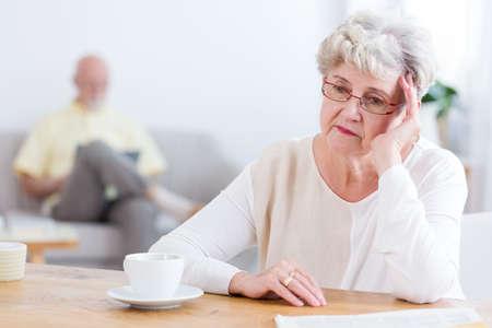 Traurige ältere Frau, die an einem Holztisch sitzt und daran denkt, sich von ihrem Ehemann scheiden zu lassen