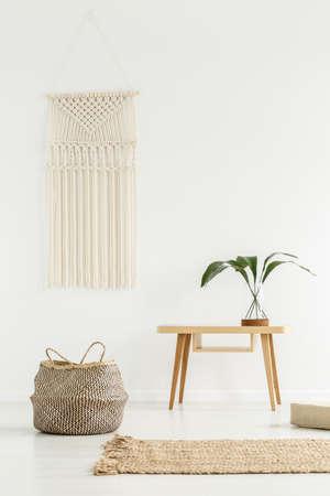 Plant op houten tafel naast een mand in wit boho-interieur met beige tapijt
