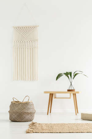 Planta en mesa de madera junto a una canasta en interior boho blanco con alfombra beige
