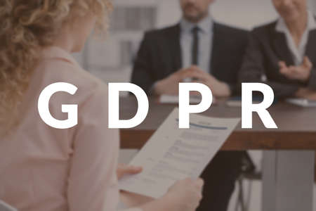 Blurred photo of a young woman holding her resume during a job interview, in front of recruiters with GDPR written on it. Data protection concept Stock Photo