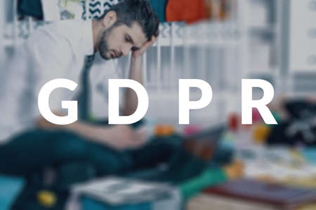 Sad businessman sitting at home with his laptop, reading about the new data security legislation and worrying about his business. GDPR concept