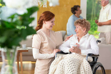 Smiling nurse taking care of happy paralyzed senior woman in the nursing house. Blurred people in the background Banque d'images - 102472259
