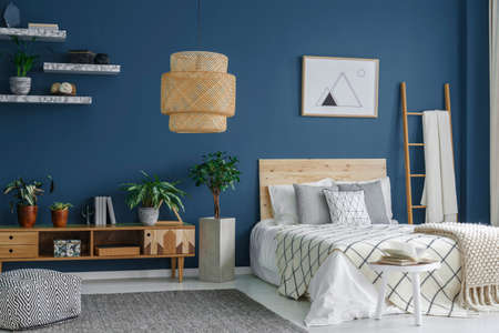 Side view of a blue bedroom interior with a modern lamp, double bed, plants and cabinet