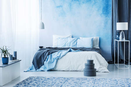 Grey boxes next to bed with blue bedding in bedroom interior with white lamp against a curtain